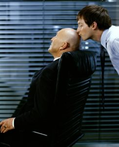 Man kissing mature man's bald head
